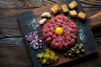 Beef tartare on a rustic wooden chopping board, above view